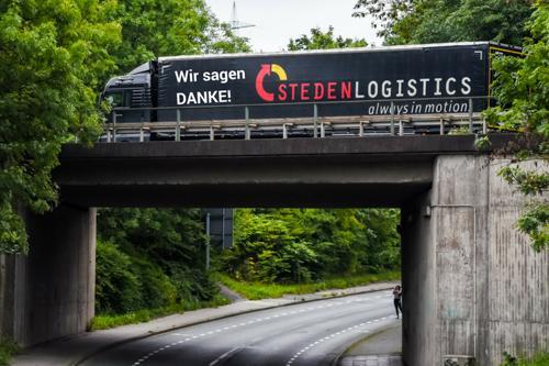 """Ein Steden-Lkw mit der Aufschrift """"Wir sagen Danke"""" auf einer Brücke"""